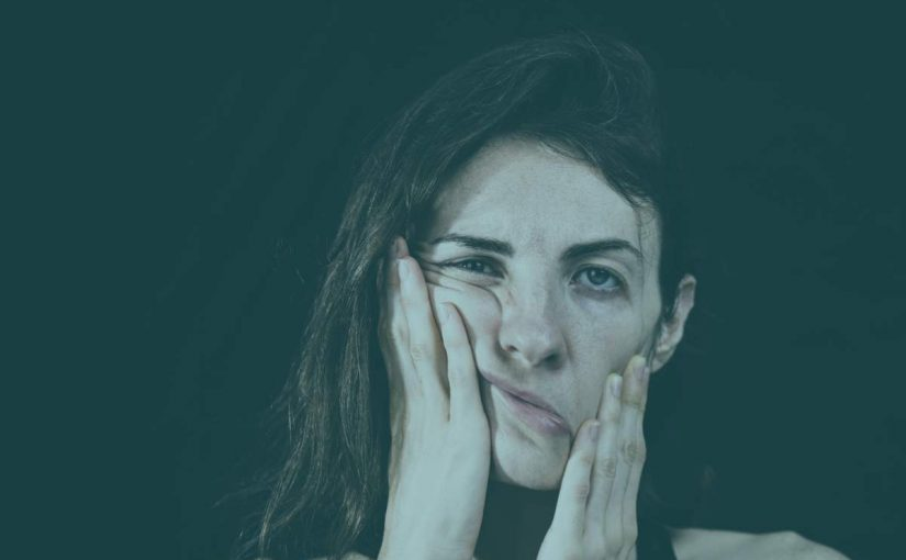 Woman holding her face in pain and frustration from the dental issue:bruxism