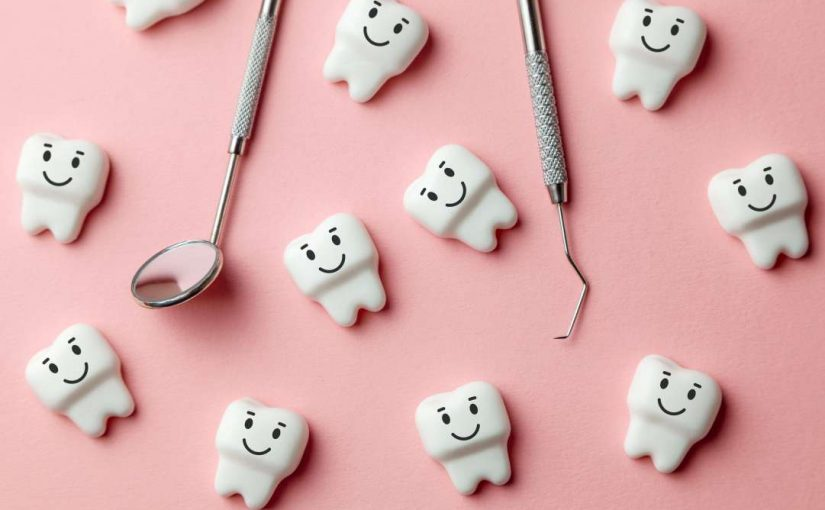 Little plastic teeth figures with smiles with a dentist's mirror and pick